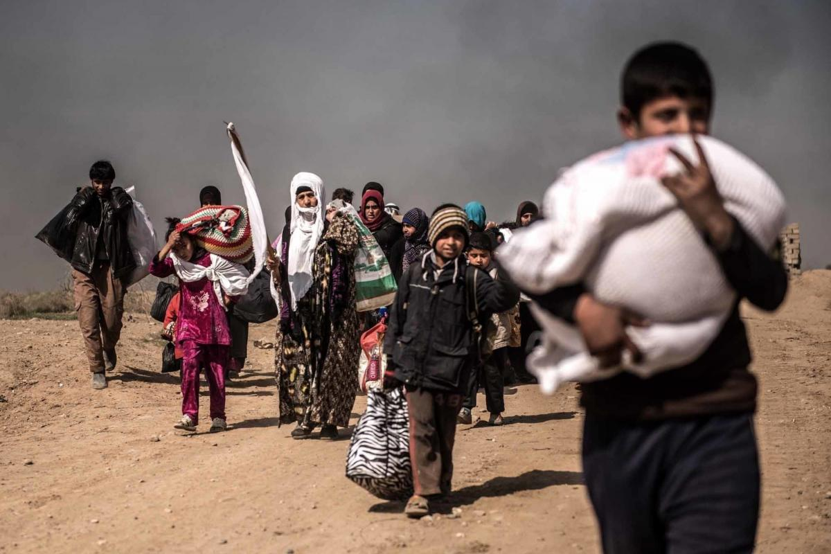 Civilians wave white flags as they flee a west Mosul suburb during heavy fighting between government forces and ISIS militants in February. Many had been warned by ISIS that they would be killed if they tried to escape.