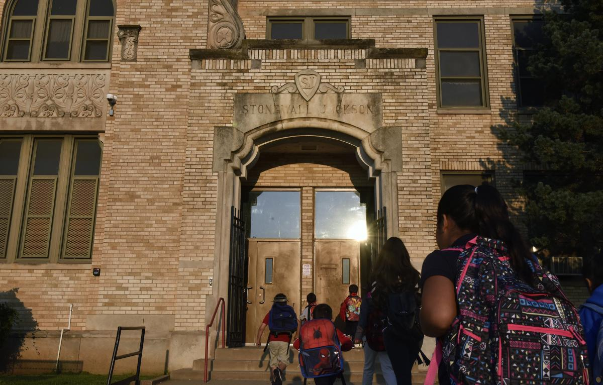 """Students walk through an entrance above which is engraved """"Stonewall Jackson"""" at Jackson Elementary School in Oklahoma City."""