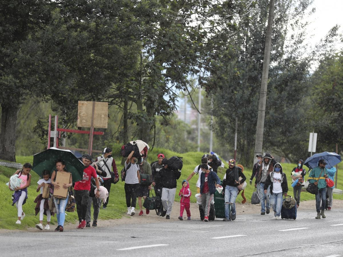 Venezuelan migrants in Colombia walk toward the border amid the coronavirus lockdown. Colombian officials say 12,000 Venezuelans have taken buses back to their home country since Colombia imposed restrictions to stop the outbreak.