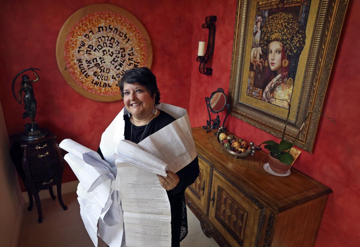 Genie Milgrom, pictured in 2013, stands in the entryway of her Miami home wrapped in a long family tree, filled with the names of 22 generations of grandmothers. Raised Catholic, Milgrom traced her family's hidden Jewish roots with the help of a trove of