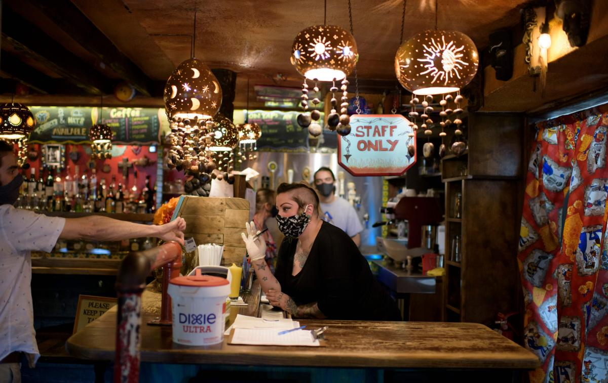 A bartender wearing a face mask and gloves checks a patron's ID at Under the Volcano in Houston last month. Texas is one of the states seeing a big uptick in coronavirus cases and hospitalizations.