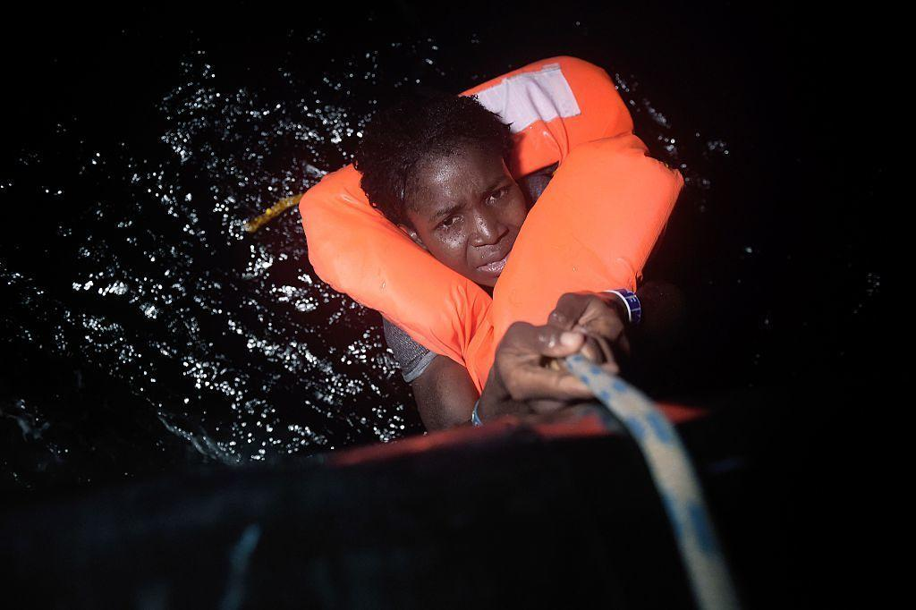 A migrant holds onto a rope during a rescue operation some eight nautical miles off Libya's Mediterranean coastline earlier this month.