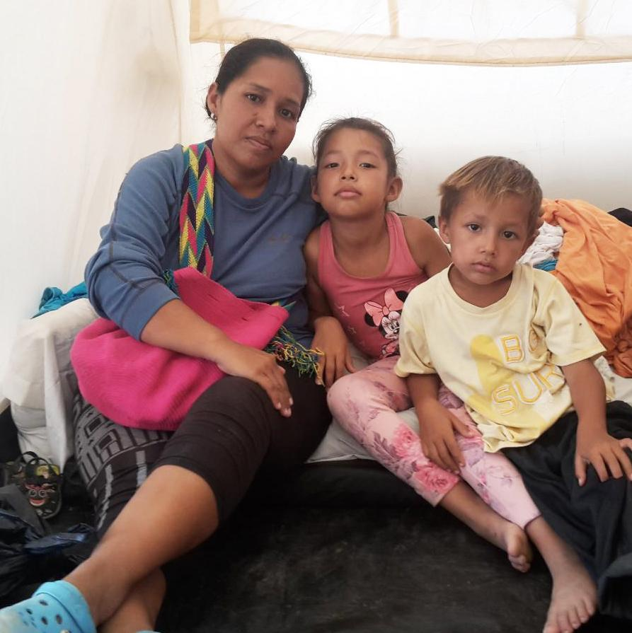 Gusmary Añez sits in a tent with two of her children. She and her husband, along with their four children, had been sleeping outdoors in Maicao, a Colombian town near the Venezuelan border. Now they live in one of 60 tents at the camp that house more tha