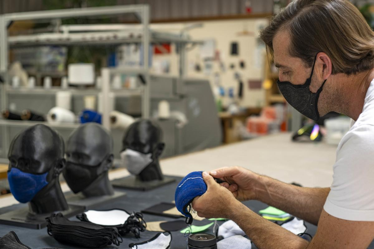 Billy Smith counts rows in the knit structure of a mask to ensure that specifications for fit and sizing meet company standards.