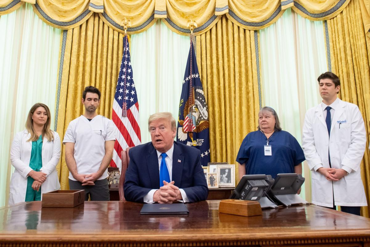 President Trump speaks about COVID-19 alongside nurses after signing a proclamation in honor of National Nurses Day in the Oval Office of the White House on Wednesday. Trump and Vice President Pence have not worn face masks during public events, which goe