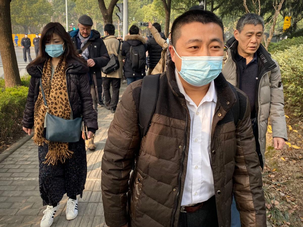 Lawyer Ren Quanniu (center), representing Chinese citizen journalist Zhang Zhan who reported on Wuhan's COVID-19 outbreak and was placed in detention since May, arrives at the Shanghai Pudong New District People's Court where Zhang is set for trial in Sha