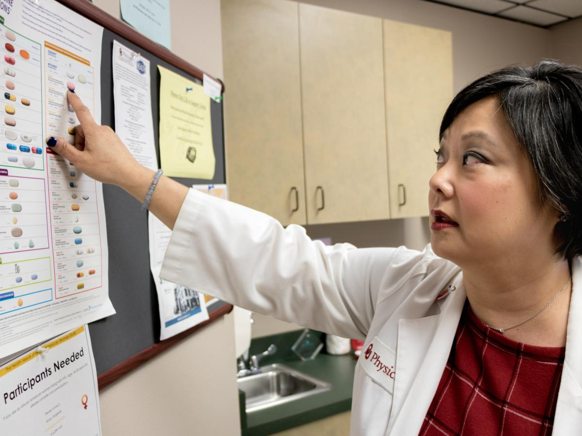 Dr. Michelle Salvaggio, medical director of the Infectious Diseases Institute at the University of Oklahoma Health Sciences Center in Oklahoma City, points to drugs used to treat HIV/AIDS. Medical advancements since the epidemic surfaced in the 1980s have