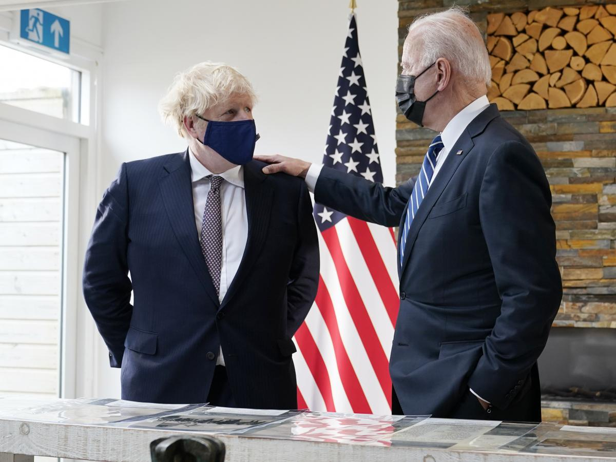 British Prime Minister Boris Johnson and President Biden talk Thursday during a meeting in Carbis Bay, England, as they look over copies of the original Atlantic Charter from 1941.