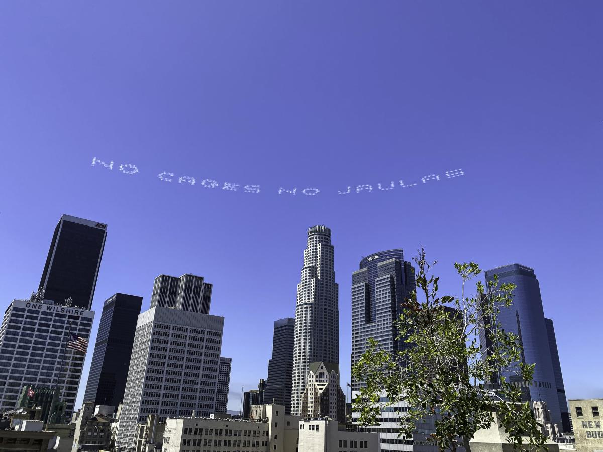 "The words ""No Cages No Jaulas"" appear over downtown Los Angeles as part of a day of activism by artists nationwide to mark the July 4 holiday. The message was designed by the artist Beatriz Cortez."