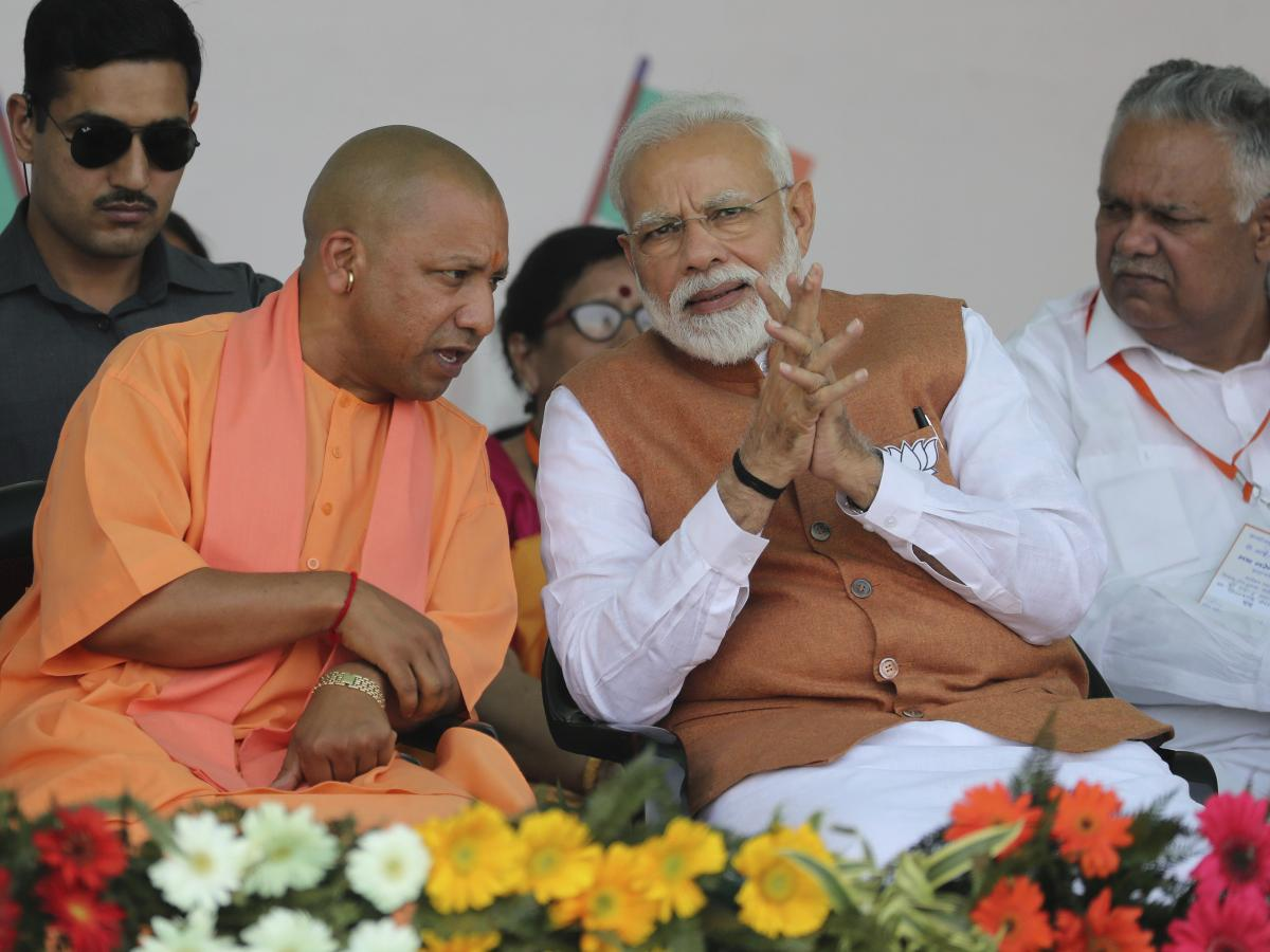 Indian Prime Minister Narendra Modi speaks with of Yogi Adityanath (left), a Hindu priest who is chief minister of Uttar Pradesh, during a campaign rally on March 28.