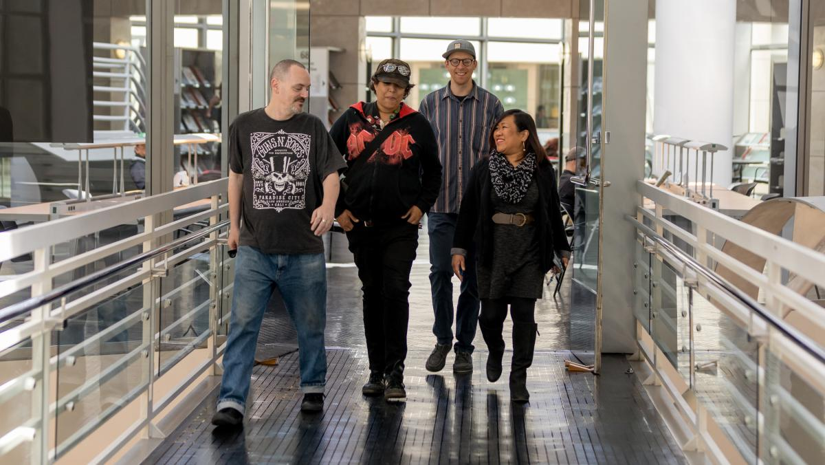 Leah Esguerra (right), who is credited with being the first social worker installed directly at a public library, strolls through the fifth floor of the San Francisco Public Library's main branch, joined by the library's health and safety associates (from