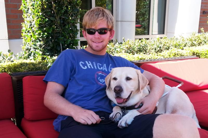 Olson sits with his guide dog, Quebec. Inspired by his experiences with the USC Trojans as a 12-year-old, Olson tried out for his high school football team.
