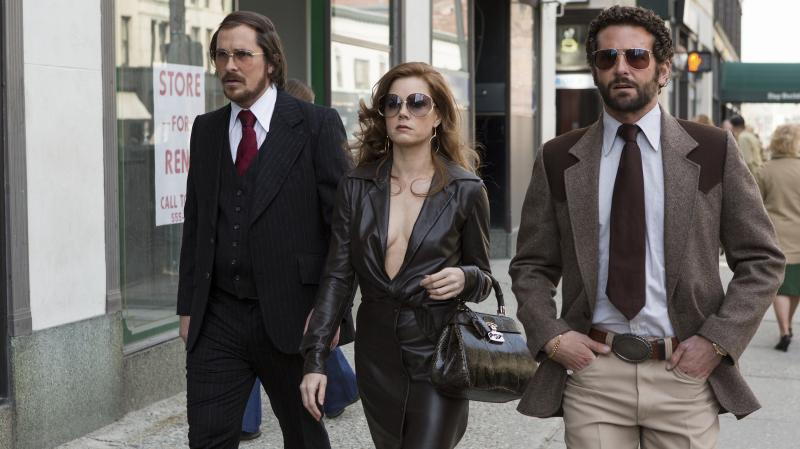 A '70s con-artist couple (Christian Bale and Amy Adams) are forced to team up with an FBI agent (Bradley Cooper, right) in American Hustle, inspired by a real-life sting targeting corrupt politicians.
