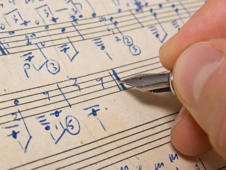 A hand writes music.