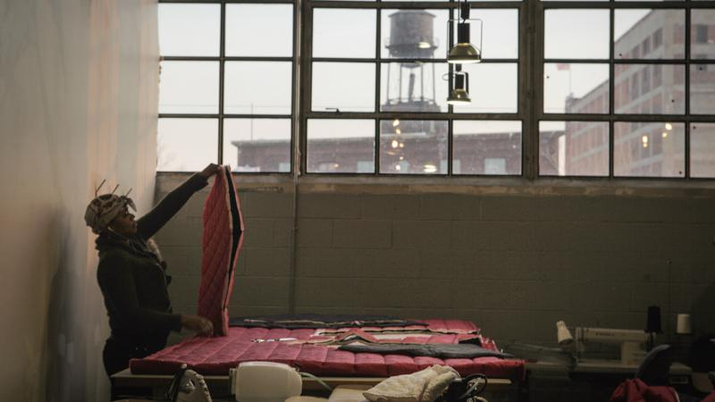 A worker with The Empowerment Plan creates a coat that will later be donated to a homeless person. The organization works inside Ponyride, a 30,000-square-foot warehouse near downtown Detroit. The warehouse hosts other local businesses, too.