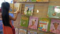 At a San Jose, Calif. library, a young reader browses a shelf of books featuring a variety of main characters: ducks, hens, white kids, black kids. Libraries help drive demand for children's books with nonwhite characters, but book publishers say there ar
