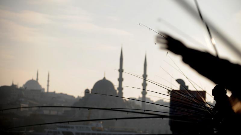 Anglers fish off Galata Bridge in Istanbul in 2011. The bridge is within site of the modest waterside restaurant Akin Balik.