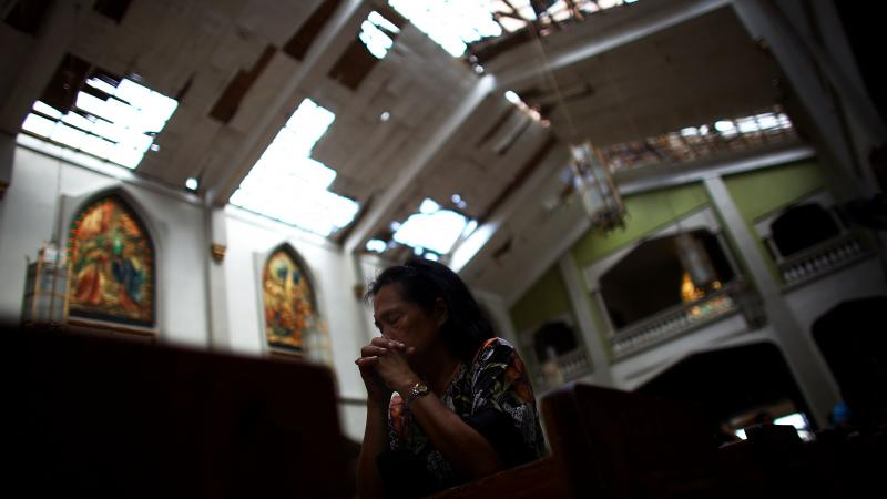 A Filipino woman prays at morning Mass at Santo Nino church, which was damaged by Typhoon Haiyan in Tacloban, Philippines, on Sunday.