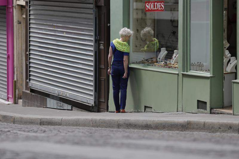 A woman walks amid both open and closed shops during a Sunday morning stroll at the Butte Montmartre in Paris, in July. Under France's Byzantine rules on Sunday trading, shops at the top of the hill are in a designated tourist area and so can open, but th