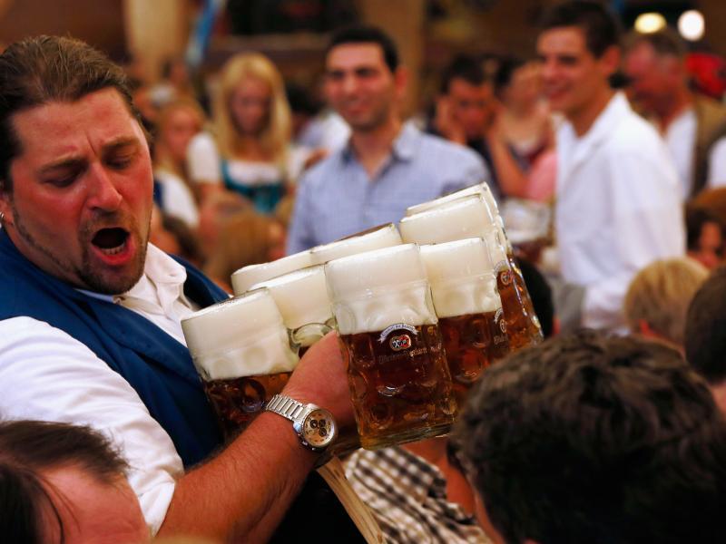 A waiter carries beer mugs during the 2012 Oktoberfest in Munich.
