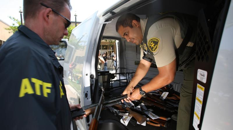 Officers transfer confiscated weapons after a news conference to announce the arrests of scores of alleged gang members and associates on federal racketeering and drug-trafficking charges in Lakewood, Calif., in 2009.