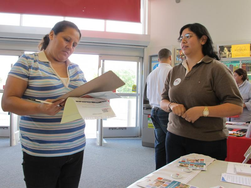 Enroll America outreach worker Rosy Mota (right) talks about the federal health care law with a CVS customer.