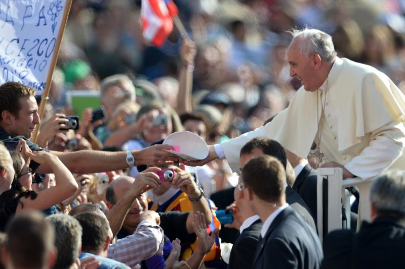 A young man gives a Catholic skullcap to Pope Francis as he greets the crowd before his general audience at St. Peter's Square at the Vatican on Oct. 16.