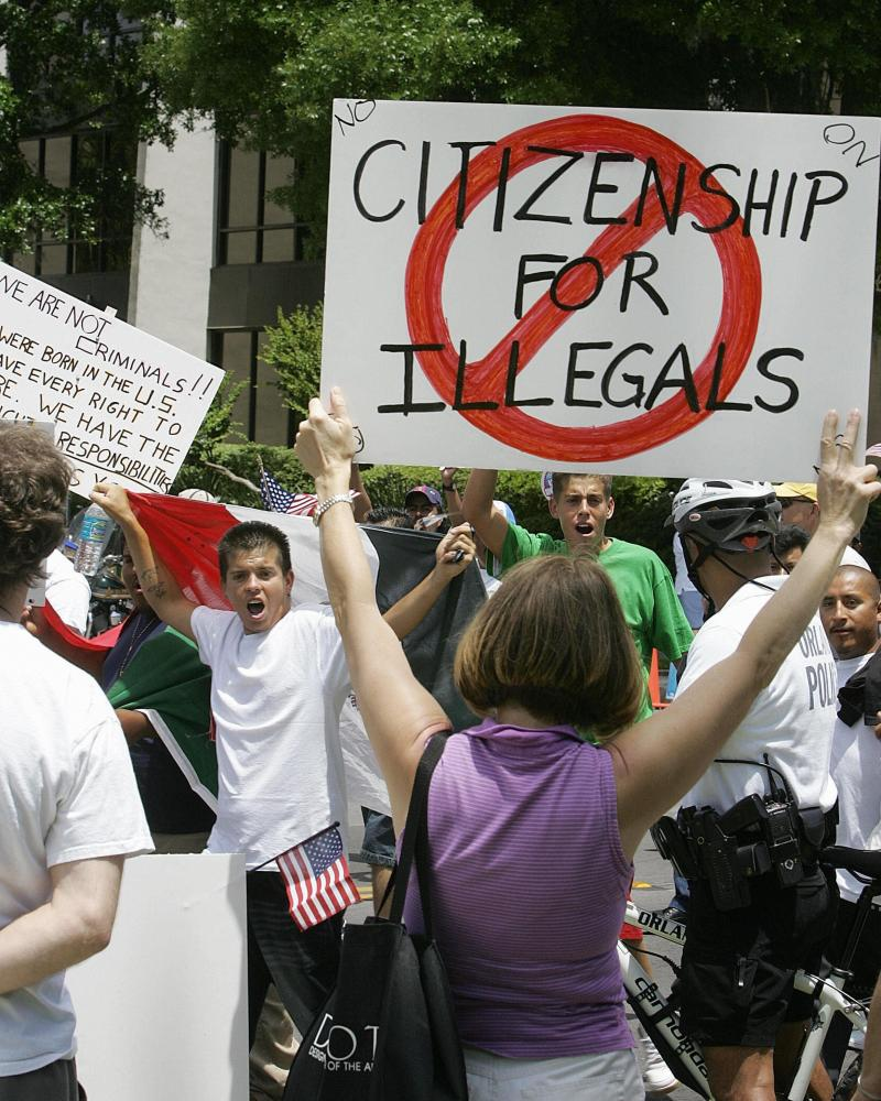 "Protesters demonstrate in downtown Orlando, Fla., on May 1, 2006. Most news outlets have long abandoned the use of the term ""illegals."""