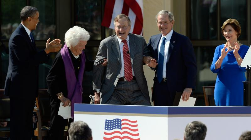 President Obama applauds as former first lady Barbara Bush and former President George W. Bush help President George H.W. Bush stand at the opening ceremony of the George W. Bush Presidential Library on April 25 in Dallas. Former first lady Laura Bush loo