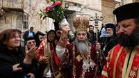 Patriarch Theophilos III, the Greek Orthodox patriarch of Jerusalem (center), splashes holy water toward worshippers after the washing of the feet ceremony in front of the Church of the Holy Sepulcher in Jerusalem in 2009, during Easter celebrations. A cr
