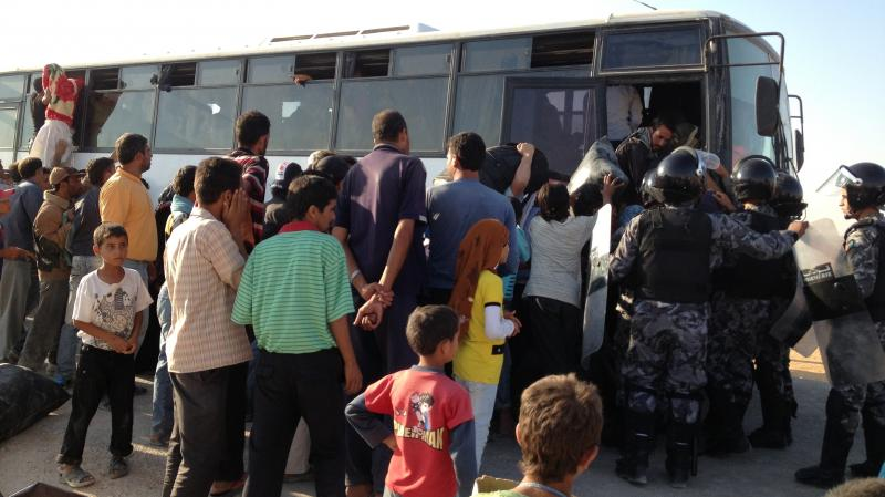 Refugees at the Zaatari refugee camp in Jordan try to squeeze on one of the buses heading back to Syria. Syrian refugees have been coming to Jordan for two years, but some are now starting to head home.