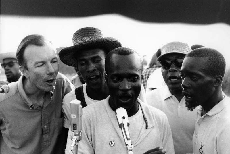 """American folk singer and activist Pete Seeger (left) adopted and helped popularize """"We Shall Overcome"""" by teaching the song at rallies and protests. Here he sings with activists in Greenwood, Miss., in 1963."""