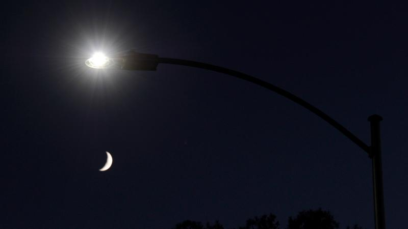 A waxing crescent moon is seen behind a streetlight with a newly installed LED fixture in 2011 in Las Vegas. The city was replacing 6,600 existing lights with the energy-efficient LEDs. It has since replaced tens of thousands more.