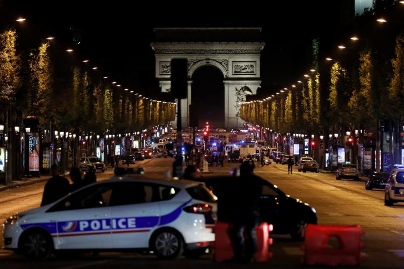 Police officers block access to the Champs Elysees in Paris after a shooting on Thursday. France's Interior Ministry said the attacker was killed in the incident on the world-famous boulevard.