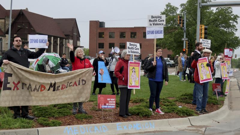 Advocates for expanding Medicaid in Kansas staged a protest outside the entrance to the statehouse parking garage in Topeka in May 2019. Today, twelve states have still not expanded Medicaid. The biggest are Texas, Florida, and Georgia, but there are a fe