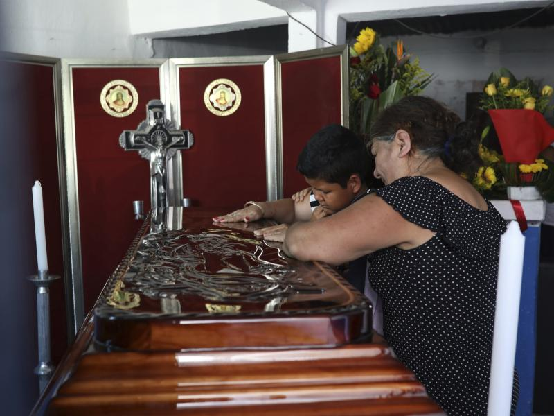 Twelve-year-old Jesús Ruiz grieves as he stands before the coffin containing the remains of his father, Mexican journalist Jorge Celestino Ruiz Vazquez, in Actopan, Veracruz, on Aug. 3. The Committee to Protect Journalists said Ruiz Vazquez was the third
