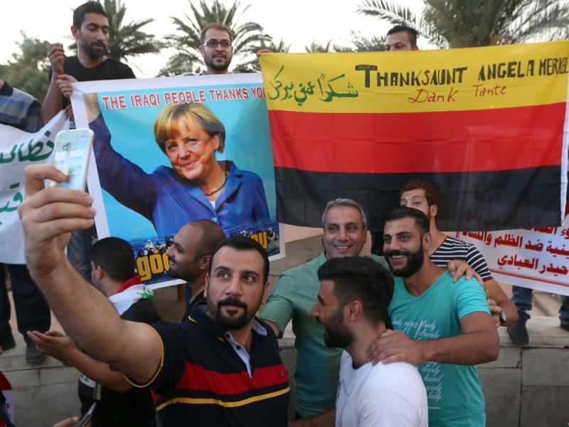 Iraqi protesters hold a picture of German Chancellor Angela Merkel during a demonstration calling for government reforms on Friday. Thousands of Iraqis are leaving the country, fleeing violence and a dire economy and drawn toward the perception of a welco