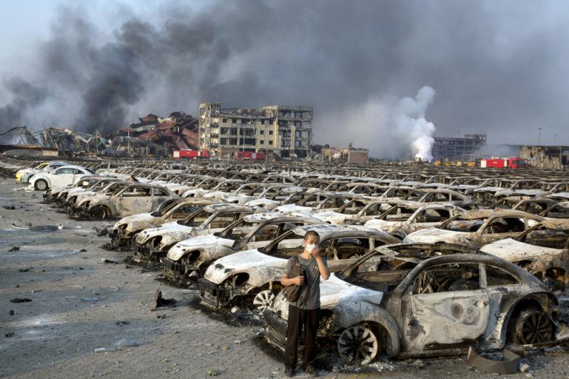 A man stands near the charred remains of new cars at a parking lot near the site of an explosion at a warehouse in northeastern China's Tianjin municipality.