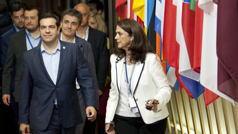 Greek Prime Minister Alexis Tsipras (front left) leaves after a meeting of eurozone heads of state Monday at the EU Council building in Brussels. The summit reached a tentative agreement with Greece for a bailout program that includes