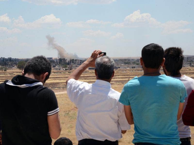 Turkish Kurds watch from the Turkish side of the border Friday as smoke rises in Kobani, Syria. Since last year, the town has seen control seesaw between Kurds and Islamic State militants.