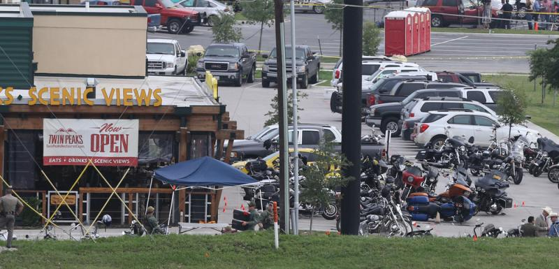 Police officers observe the scene at Twin Peaks restaurant in Waco, Texas, the site of the recent motorcycle gang-related shooting.