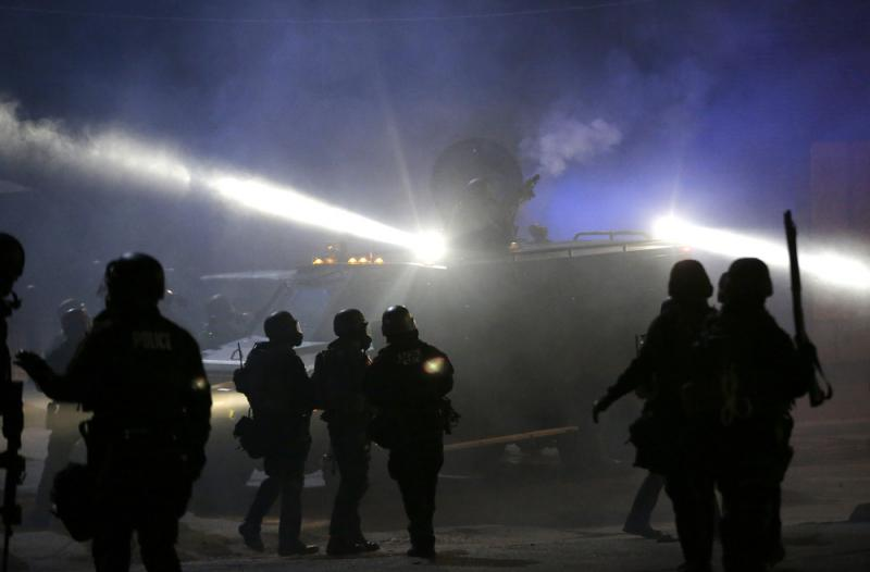 Police in riot gear stand around an armored vehicle as smoke fills the streets of Ferguson, Mo., in November 2014.