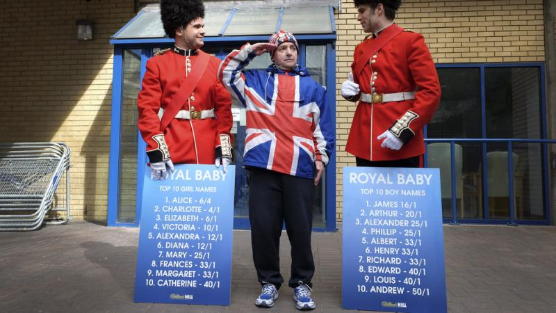 Royal supporter John Loughrey salutes with men dressed as soldiers carrying boards with proposed baby names outside the Lindo Wing of St Mary's Hospital in London on Friday.