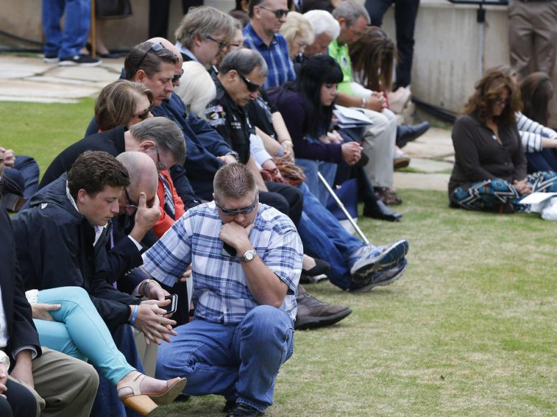 Spectators bow their heads during a moment of silence during a ceremony to commemorate the 20th anniversary of the Oklahoma City bombing at the Oklahoma City National Memorial, on Sunday.