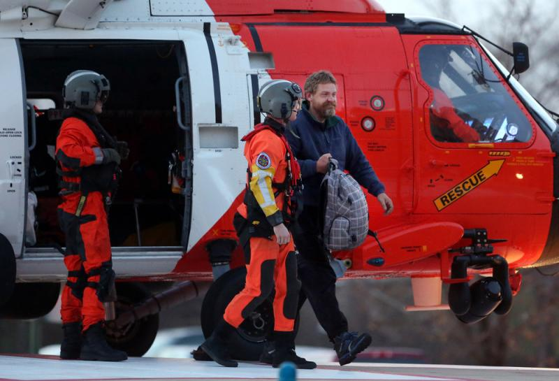 Louis Jordan (right), walks from the Coast Guard helicopter to the Sentara Norfolk General Hospital in Norfolk, Va., after being found off the North Carolina coast, on Thursday. His family says he sailed out of a marina in Conway, S.C., on Jan. 23, and ha