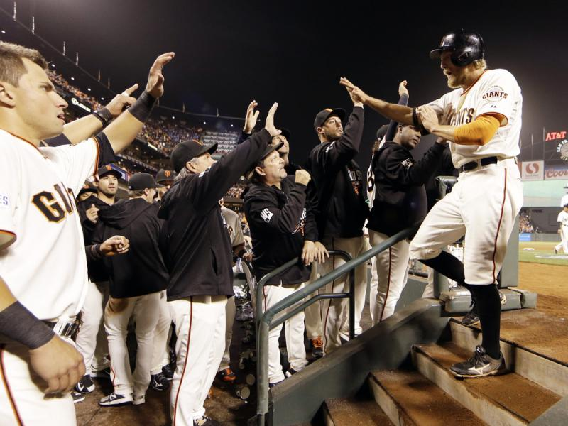 San Francisco Giants' Hunter Pence is congratulated in the dugout after scoring during the sixth inning of Game 4 of the World Series against the Kansas City Royals on Saturday.