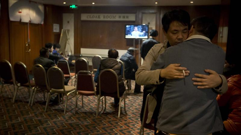 Relatives of Chinese passengers aboard the missing Malaysia Airlines flight comfort each other as they wait for a news briefing by airline officials at a hotel ballroom in Beijing on Thursday.