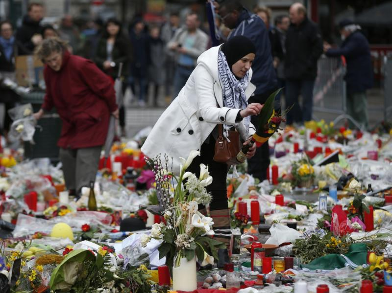 A woman helps readjust the tributes in the Place de la Bourse, left for the victims of the recent bomb attacks in Brussels.