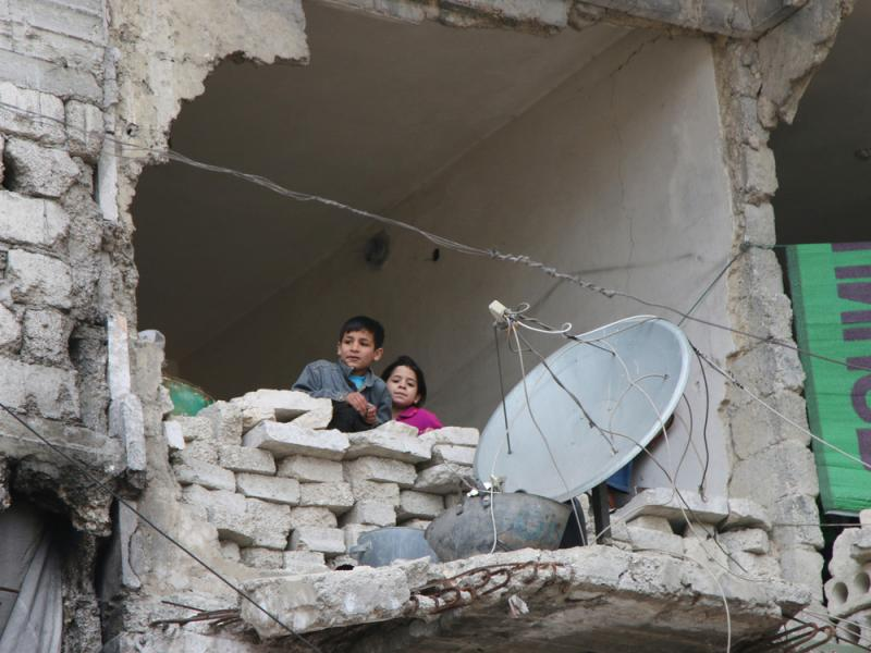 Children peer from a partially destroyed home in Aleppo, Syria in February. Syria's largest city used to be its economic locomotive, now it is has become an emblem of its stalemated civil war.