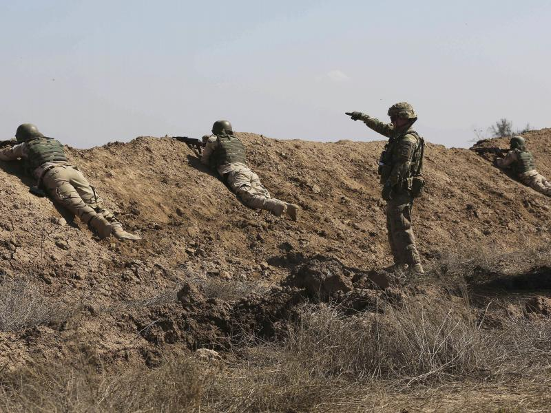 A U.S. soldier (standing) helps Iraqi security forces improve shooting skills at Camp Taji, north of Baghdad, in 2015.